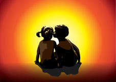 Sun children. Boy and girl watching as the sun disappears behind the horizon Royalty Free Stock Images