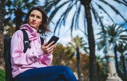Владение девушки в руках мобильном телефоне, типе сообщении человека на смартфоне, ослабляет туристские перемещения планируя откл стоковое фото rf