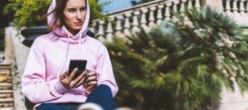 Владение девушки в руках мобильном телефоне, типе сообщении человека на смартфоне, ослабляет туристские перемещения планируя откл стоковая фотография