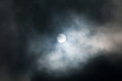Sun between clouds. Sun in the haze among dramatic dark clouds Royalty Free Stock Photos