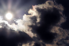 Sun and clouds. Heavy clouds with bright sun lens flare Stock Photos