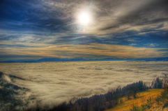 Sun and clouds. An excentric view from the top of the mountains.The clear sky above you and the foggy clouds below Royalty Free Stock Photo