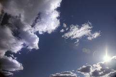 Sun and clouds. The summer sun peeking out behind the clouds in a dark blue sky Royalty Free Stock Photos