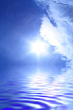 Sun and clouds. Sun among clouds in the blue sky and reflection of the sky in water Stock Photos