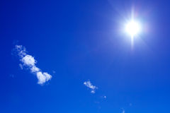 Sun and clouds on blue sky royalty free stock photo