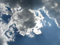 Sun in the clouds. Blue sky, bright sun, gray clouds Stock Image