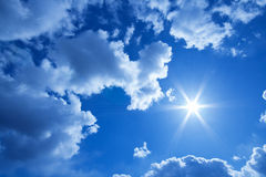 Sun and clouds in a blue spring sky Royalty Free Stock Photos