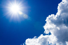 Sun and clouds in dark blue sky. This image can be used as a background and in different other projects Royalty Free Stock Photo