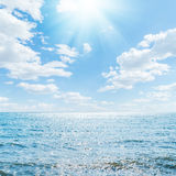 Sun in clouds over blue sea. Sun in sky with clouds over blue sea Royalty Free Stock Image