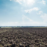 Sun in clouds over field after harvesting Royalty Free Stock Image