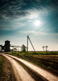 Sun and clouds over field with road. Royalty Free Stock Image