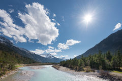 Sun and clouds over flowing river Stock Photography