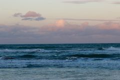Sun in the clouds over the waves Royalty Free Stock Photography