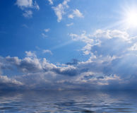 Sun, clouds and sea. Sea view - sun and clouds against blue sky Stock Image