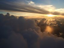 Sun through the clouds. Over the sea seen from plane Royalty Free Stock Photos