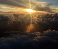 Sun through the clouds. Over the sea seen from plane stock photos