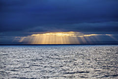 Sun through clouds to the sea Stock Image