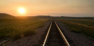 Railroad Tracks Reflect Sunrise Rural American Transportation. The sun comes up revealing a transportation themed image with train tracks Royalty Free Stock Images