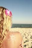 Of sun cream on the female back on the beach Stock Photo