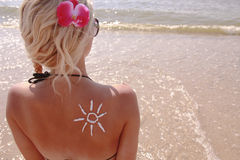 Of sun cream on the female back on the beach Royalty Free Stock Photos