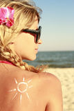 Of sun cream on the female back on the beach Stock Images