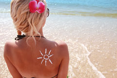 Of sun cream on the female back on the beach. A of sun cream on the female back on the beach Royalty Free Stock Images