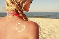 Of sun cream on the female back on the beach Stock Photos