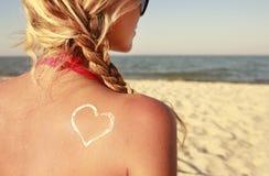 Of sun cream on the female back on the beach. A of sun cream on the female back on the beach Stock Photos