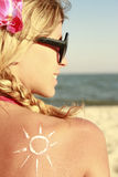 Of sun cream on the female back on the beach Stock Photography