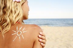 Of sun cream on the female back on the beach. A of sun cream on the female back on the beach Royalty Free Stock Image