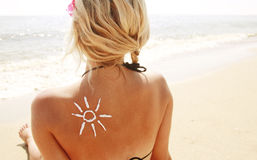 Of sun cream on the female back on the beach Stock Photo