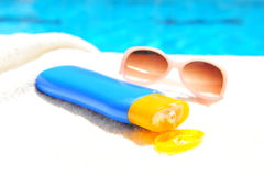 Sun cream and sunglasses. Bottle of sun cream and sunglasses on towel with blue swimming pool in background Royalty Free Stock Photography