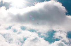Sun and cumulus white clouds against a beautiful blue sky, fly plane royalty free stock photo