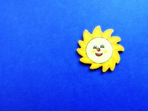 Sun cut from wood. Yellow sun on blue background, wood carving Stock Image