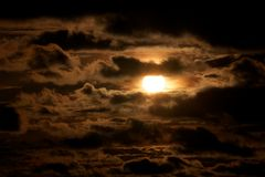 Sun through the dark clouds Stock Photography