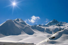 A sun day is in mountains. Snow-bound mountain peaks, bright sun and clouds Stock Photos