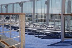 Sun Deck on a Cruise Ship. Lounge chairs lined along the sun deck of a large cruise ship Stock Image