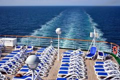 Sun Deck on Cruise Ship. Sunny deck with sun beds at stern of cruise ship, with wake trailing into the distance Stock Images