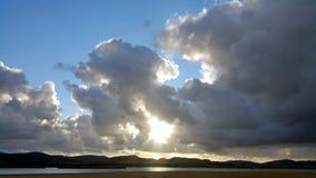 Sun in den Dunkelheitswolken über Fluss Stockbilder
