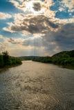 Sun in den Wolken über dem Fluss Stockfoto