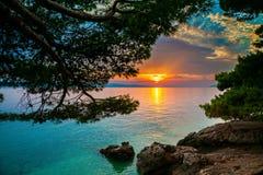 Sun, der über das adriatische Meer in Brela einstellt Stockfotografie