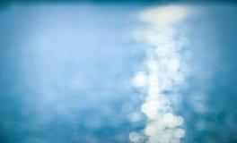 Sun, der über das Wasser im blauen Ton nachdenkt Stockbild