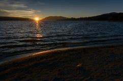 Sun, der über den Big Bear See beleuchtet herauf den Felsen auf dem Strand einstellt Stockfotos