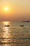 Sun, der über Kayakers einstellt Stockfotografie