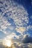 Sun, der durch dynamische Wolken scheint. Stockfotos