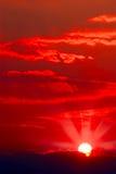 Sun, der durch niedrige Wolke scheint Stockbild