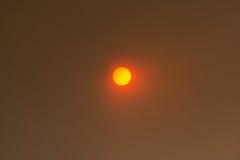 Sun, der durch Rauchwolken vom verheerenden Feuer späht Lizenzfreie Stockbilder