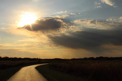 Sun, der durch Wolken auf einer einsamen Straße bricht Lizenzfreies Stockfoto