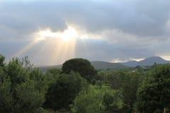 Sun, der durch Wolken strömt Lizenzfreie Stockfotos