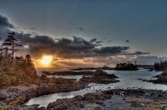 Sun, der durch Wolken vor Inseln entlang Küste emporragt Stockfotografie